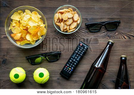 watching movies concept with chips, beer and zapper on wooden table background top view