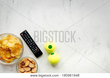 TV remote control, balls and snacks on white desk background top view space for text