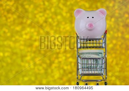 Closeup of pink piggy bank pig standing on mini shopping push cart with US 20 $ in it, on blurred yellow Bokeh background copyspace