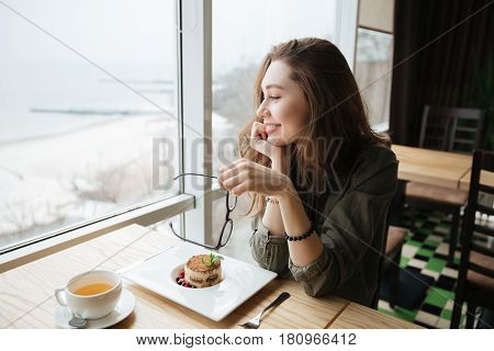 Image of young cheerful lady with long hair holding glasses sitting in cafe. Looking aside.