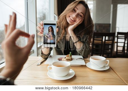 Smiling woman showing photo to her friend using phone. Showing gesture okay
