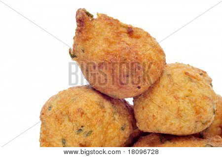 closeup of a few cod fritters on a white background