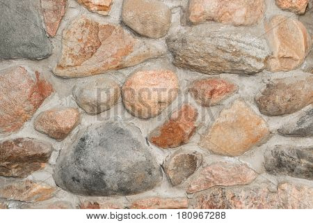 Wall of granite boulders on cemented masonry