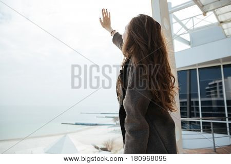Young woman raising her hand to sun while walking near sea
