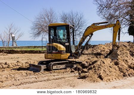 A small excavator is digging sand for a new road