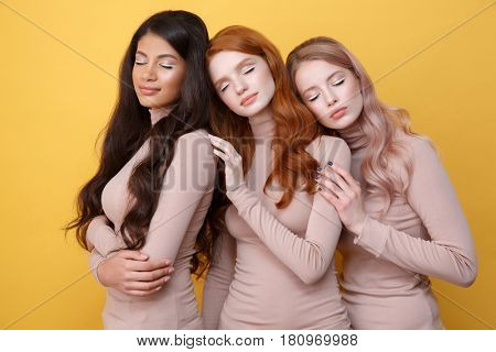 Three smiling ladies posing in studio with closed eyes over yellow background