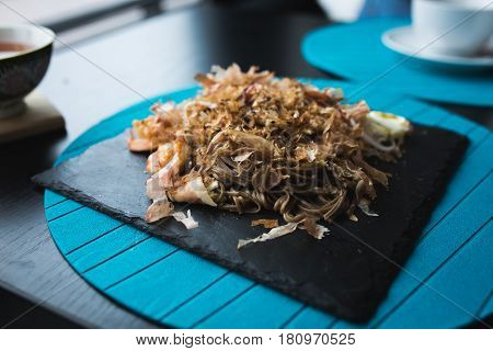 Buckwheat noodles with shrimps and shavings of tuna with sauce on black plate. Asian food background. Eating concept. Restaraunt place with wooden table. Flare copy space for text design. poster
