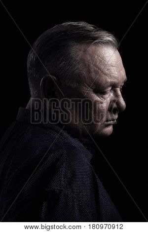 Classic profile portrait of aged man with closed eyes wearing shirt against black background - retirement concept