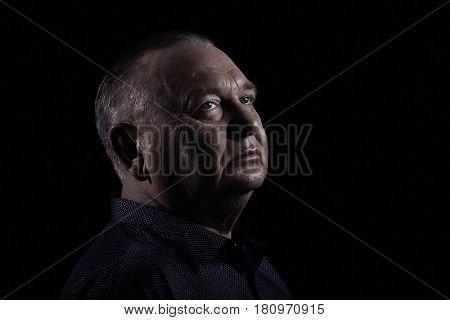 Close up portrait of aged man wearing shirt against black background - retirement concept