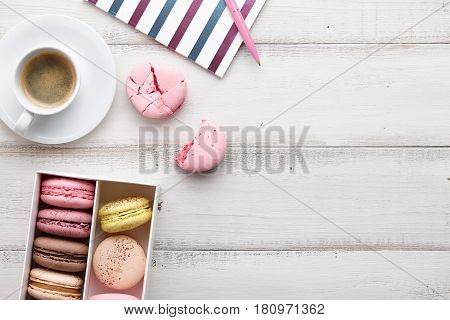 Woman's workspace with notebook, macarons, yellow tulips and a cup of coffee