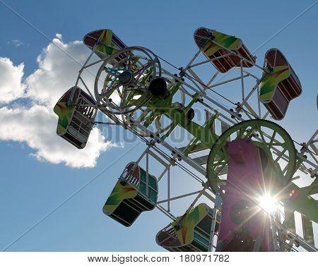 Amusement Park Ride at the Fair Against a Blue Sky with Sunburst