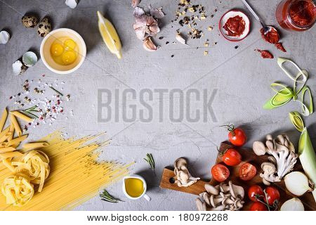 Italian pasta food frame, Spaghetti, linguine and penne with ingredients over grey concrete background. Top view, copy space, flat lay.