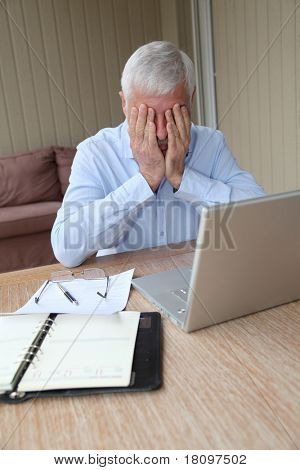 Desperate senior man in front of laptop computer