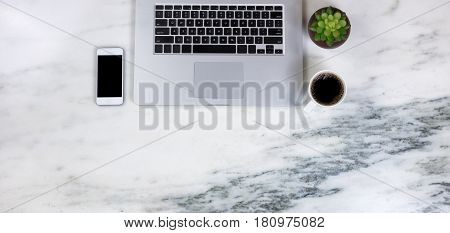 Flat lay of a partial laptop plant smartphone and dark coffee on natural marble desktop