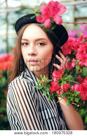 Tender sweet young woman with long chestnut hair and black hat enjoying azalea flowers in greenhouse. Romantic mood concept.Selective focus.