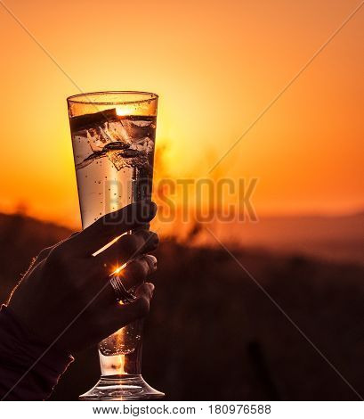 Picture of a drink with sunset as  background sundowner in South Africa.