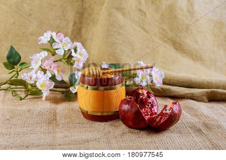 Honey Jar And Fresh Apples With Pomegranate Over Bokeh Background