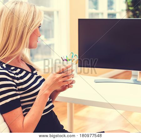 Young Woman Sitting In Front Of Big Monitor
