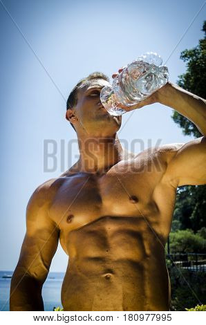 Handsome young muscle man drinking water from plastic bottle at the seaside, outdoors, showing muscular pecs and torso in front of the sea