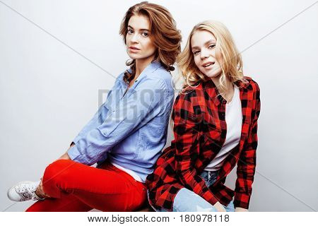 two pretty blond woman having fun together on white background, mature mother and young teenage daughter, lifestyle people concept close up