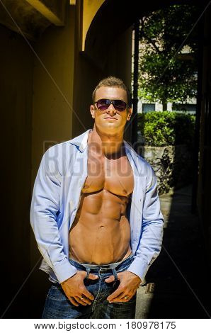 Attractive young muscle man outdoors with shirt open, showing muscular pecs, abs and torso