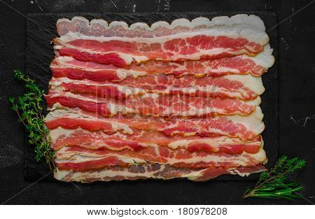 Raw sliced bacon ready for cooking on dark black concrete background. Ingredients for raw bacon cherry tomatoes thyme rosemary. Top view from above and copy space.