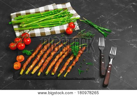 Asparagus baked grill wrapped in bacon. Ingredients for asparagus wrapped in bacon cherry tomatoes parsley thyme rosemary fresh asparagus. Dark black background.
