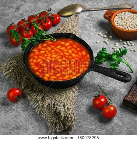 Baked stewed white beans in a cast-iron frying pan in tomato sauce. Ingredients for stewed beans are tomatoes parsley raw beans rye bread burlap spoon. Gray concrete background.