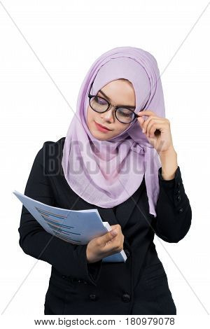Beautiful modern Young Asian Muslim business woman looking at reportsisolated on white background.