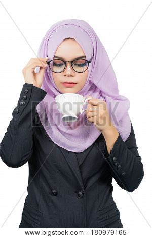 Beautiful modern Young Asian Muslim business woman holding a white coffee cup and look at coffee cupisolated on white background.