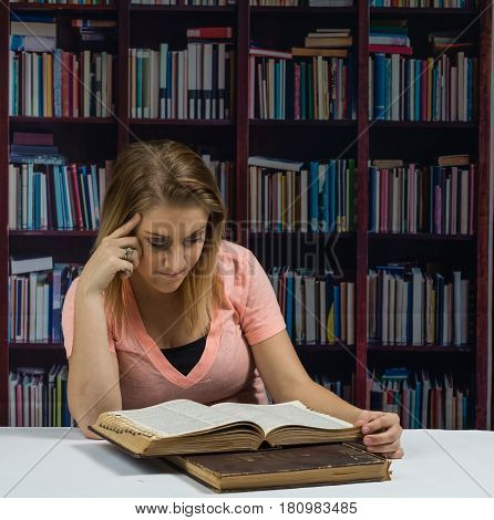 Young woman thinking while reading, hand on forehead.