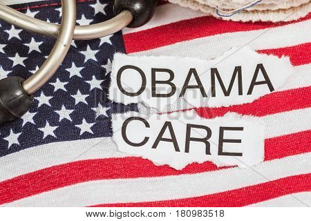 Obama Care on torn paper laying on an American flag with a stethoscope
