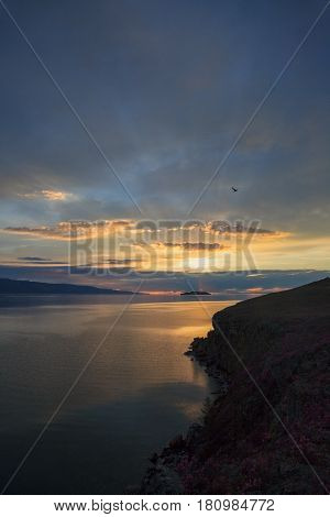Beautiful dramatic sunrise over water surface, view from the cape
