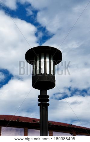 streetlight of black color against the background of the blue sky with clouds and the small site of a roof
