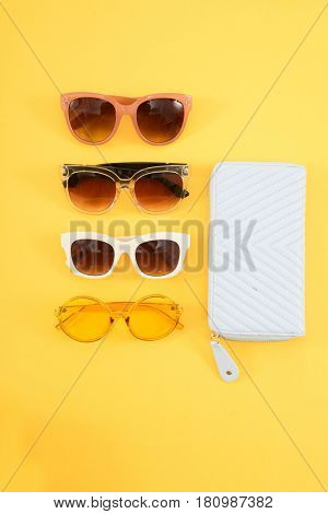 handbag and four glasses on a yellow background