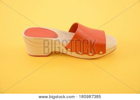 female wooden shoe-yellow background