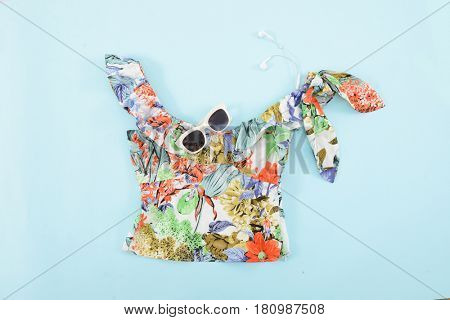 Fashion. Summer woman accessories-Summer floral clothes with sunglasses on blue background