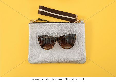 handbag and glasses on a yellow background