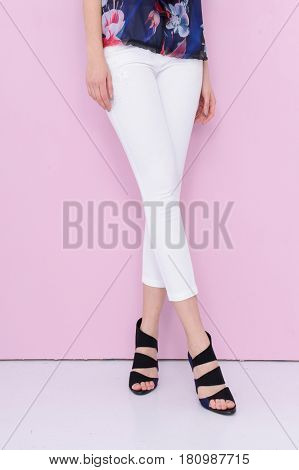 Woman long legs wearing floral dress, high heels on pink background