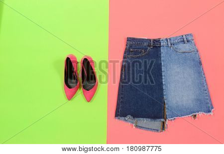 Blue denim skirt with red shoes isolated yellow background