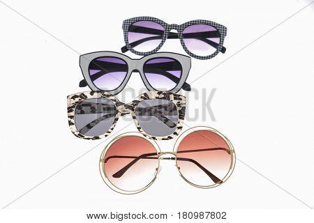 Fashionable four sunglasses on white background