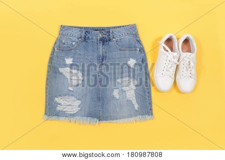 Blue denim skirt with shoes isolated yellow background