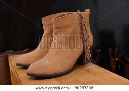 Shoe shop - boots on long wooden cube