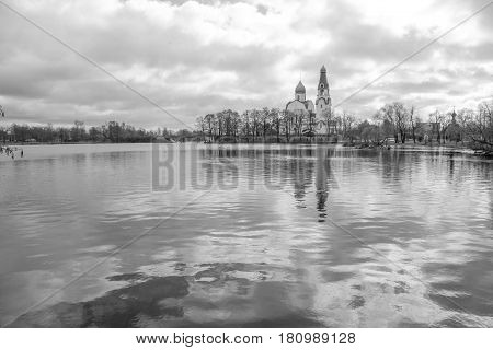 Leningrad region. City Sestroretsk- 10.04.2017: Temple standing on the river bank with reflection in the water