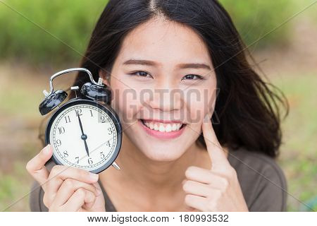 baby face timeless cute asian women girl with young skin look with clock time.