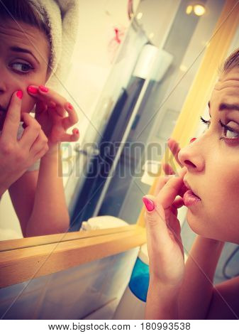 Woman looking at her reflection in mirror thinking about her complexes having serious face expression analyzing face skin complexion squeezing pimples