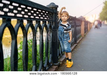 The boy is leaning on the fence. Alley in the park along the coast. The child walks and stands in a funny pose posing on the camera playing and having fun.