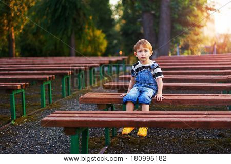 The boy sits on a bench and thinks about something. Outdoor theater in the park. Benches for spectators. Summer sunny evening. A child in yellow sneakers is sitting on a bench