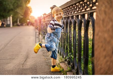 The boy is standing on one leg. A child is standing at a fence in a city park. The boy is playing and smiling posing and croaking. Sunset on a summer evening.
