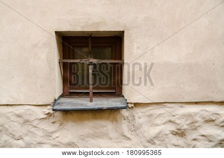 A small window with an old grating in the wall. The grate is made in the form of two crossed steel bars.